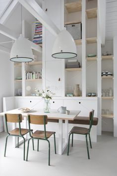 big hanging industrial pendants. white dining table. simple school style chairs.