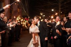 Newlyweds Tess & Ed kiss under a canopy of #sparklers after their #wedding reception in downtown #Raleigh. The bride is wearing #ModernTrousseau's #Bailey gown with #featherstole from the designer's #Charleston flagship boutique.   Image courtesy of # AJDunlopPhotography. Wedding featured on #TheLovelyFind.com