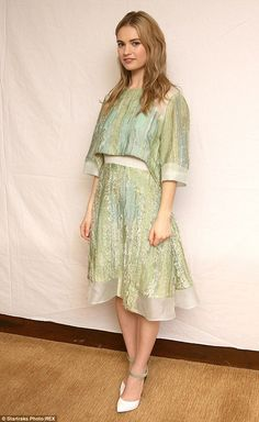 Serene in green: Lily James stands out in a shimmering pistachio-coloured crop top and skirt at a Cinderella photocall