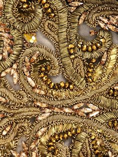 Detail of Alexander McQueen's stunning 'Duchess' dress in black silk with gold metal thread stitching and gold beads on a nude mesh