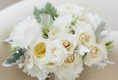 Made of white peonies, ivory Patience garden roses, white Majolica spray roses and dusty miller, this bridal bouquet is perfect for an outdoor affair. Designed by Peony & Plum.