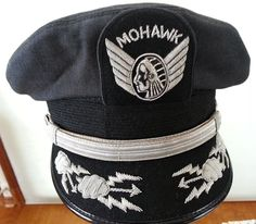 You are going to LOVE this special, truly rare find. A genuine vintage pilots cap from the long defunct Mohawk Airlines! The detailing is superb and the hat is in awesome condition. Mohawk merged with Allegheny Airlines in the 1970s, ultimately becoming part of US Air. The silver wings and Indian are composed of thick threads of silver bullion. Highly unlikely that you will see a hat like this again.