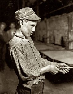 U.S. Carrying-In Boy: October 1908. Grafton, West Virginia. Glassworks carrying-in boy at lehr (annealing furnace), fifteen years old. Has worked for several years. Works nine hours. Day shift one week, night shift next week. Gets 1.25 per day // Photo  by Lewis Wickes Hine.