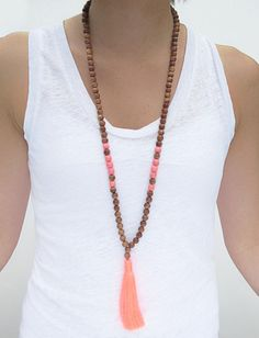 Boho style at its best. This wooden bead tassel necklace is accented with coral beads and a neon coral tassel. This necklace can make your outfit! Materials: wood, acrylic & tassel Length: 34""