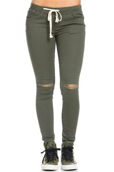 Distressed at the knee. A skinny, olive colored mid-rise jogger jean featuring…