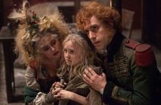 Les Mis (2012)   Movie Still: Helena Bonham Carter (Mme. Thenardier), Isabelle Allen (young Cosette) and Sacha Baron Cohen (M. Thenardier) in the big screen adaptation of the acclaimed musical Les Miserables.