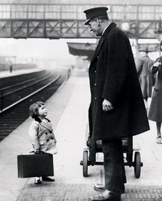 a very young passenger asks a station attendant for directions, on the railway platform at bristol, england, 1936.