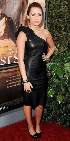 Look of the Day › March 26, 2010 WHAT SHE WORE For the L.A. premiere of The Last Song, the singer-actress rocked a single-shoulder Thomas Wylde leather dress WHY WE LOVE IT Miley Cyrus put a ladylike spin on a tough-girl trend by choosing a demure knee-length leather dress with ruffled embellishment. Try pairing a leather pencil skirt with a ruffled button-down to get her edgy-but-feminine look.
