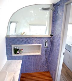 Luna Blue Moon Trailer Airstream Bathroom shower wood floor tile walls window sing counters shampoo