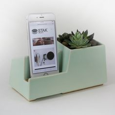 This large multi-functional phone dock accommodates a wide variety of today's smart phones including the iPhone, Galaxy models, Motorola Droid, and many more.  Made of white stoneware, the Delta Phone Dock features a large compartment for small plants or desk accessories.