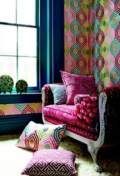 A strikingly colourful wallpaper and coordinating scatter cushions create a wonderful richness.