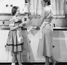 Mom and daughter hand washing dishes together. In dresses no less.
