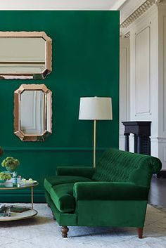 Green and gold are a match made in heaven. This green sofa and matching wall are striking with gold accessories, like those lovely mirrors.