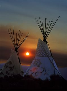 Sun rising between two teepees at Taos Drum, Taos, New Mexico