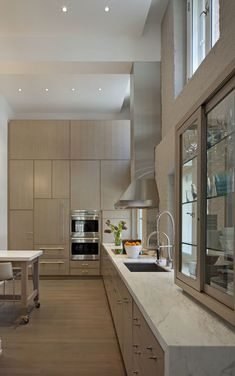 Tribeca loft ktchen, pale wood cabinets,  marble waterfalling at end of counter run