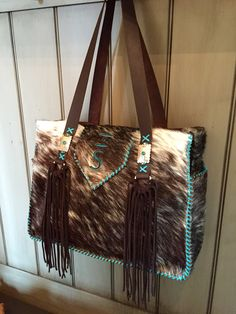 A Buckaroo Diaper Tote with the customers' brand in turquoise suede, hand cut chocolate brown suede fringe, and stitched with turquoise leather lace. gowestdesigns.us