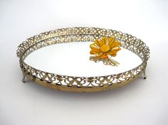 Cute small round footed gold metal vanity mirror tray. Sits on three feet. Perfect for bedroom dresser or bath. Great for jewelry or perfumes.