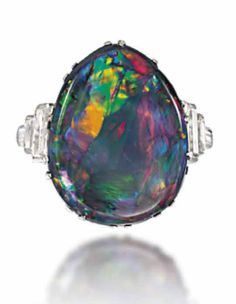 AN ART DECO BLACK OPAL AND DIAMOND RING  The pear shaped opal claw-set between triple baguette-cut diamond shoulders, raised on a pierced gallery, to a plain hoop, circa 1930.