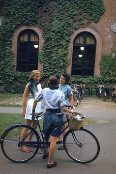"""""""A student with a bicycle talks with two classmates near an ivy-covered wall on the campus of Smith College, Northampton, Massachusetts, Photo by Peter Stackpole. Prep School Style, Estilo Ivy, Mode Disco, Theodora Home, Smith College, College Life, College Goals, College Aesthetic, Sufjan Stevens"""