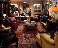This room looks so cozy and lived-in. I really like the different shades of red and yellow, also a bit of leather with the various fabric covered pieces.