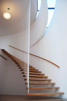 wooden staircase with white vertical supports that almost look like rope from a distance.