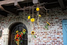 Dancing Sunflowers hang by rafia from a curly willow armature for a Committment Ceremony at the Historic Casa Feliz Home Museum.  Designed by Lana with Fairbanks Florist.  Art Faulkner Photography.