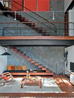 Dois lances de escada interligam a garagem, na parte alta do terreno, à sala. Mãos-francesas metálicas fixam cada um dos degraus de ipê na parede.