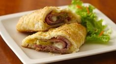 Cuban Calzones - Ingredients are 2 pillsbury grands frozen buttermilk biscuits, 1.5 teaspoons yellow mustard, 1.5 teaspoons mayo, 2 oz. sliced pork, 2 oz. sliced ham, 4 round dill pickle slices, 2 tablespoons shredded swiss cheese, 1 egg and 1/2 teaspoon dried minced onion!