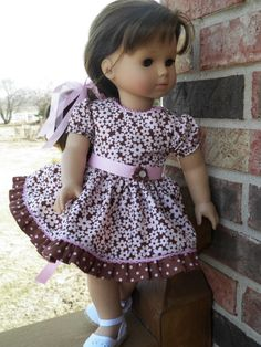 The Perfect Party Dress--Full gathered skirt with a ruffle in a coordinating fabric accented with pink grosgrain ribbon sash with a tiny yoyo with button in center  embellishment; pink bias with crocheted looking loops on edge is inserted between ruffle and skirt and along neckline to compliment the pink in the fabric
