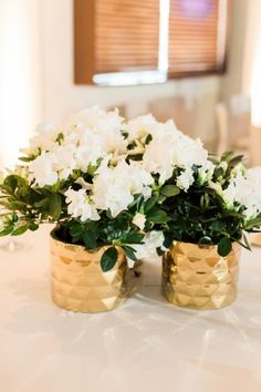 White centerpieces in gold containers | Romantic Navy & Blush Oklahoma Wedding via TheELD.com