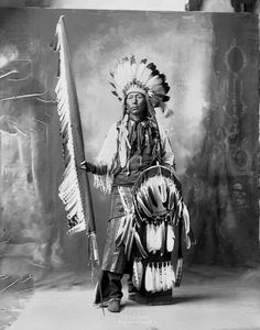 Hachasnacha (Little Chief), Arapaho, in Partial Native Dress with Ornaments and Headdress and Holding Shield and Feather Lance - Frank A Rinehart - 1898
