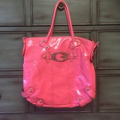 Pink Leather Guess bag  Large sized hand bag with removable shoulder strap and silver hardware. Some tarnish on the front guess emblem. Zippered top closure with pockets inside. Lining in fair condition with one minor tear about 1/2 an inch. Shows in last pic above zipper pocket. Priced to sell! Guess Bags Satchels