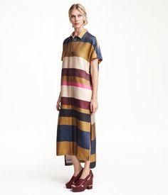 Hafif parlak dokuma kumaştan, yakalı, kısa kollu, önü gizli düğmeli, yanları yırtmaçlı, düz kesimli uzun gömlek elbise. Arka kısmı biraz daha uzun. Astarsız. Çizgilerin görünümü elbiseden elbiseye değişiklik gösterir.
