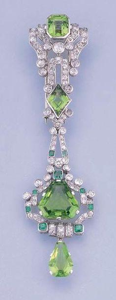 AN ART DECO PERIDOT, ESMERALDA Y DIAMANTE BROCHE / COLGANTE Diseñados como broche clip y colgante desmontable, los cuatro peridotos vari-cut dentro de calado de corte antiguo de diamante y esmeralda envolvente geométrica, alrededor de 1925, 10.9 cm. alto.