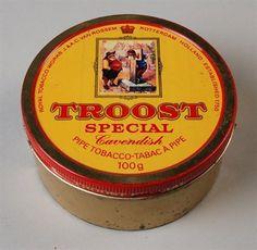 Cilindrisch geel tabaksblik (A) met rode letters en los deksel (B) van Van Rossem, productnaam Troost (special)