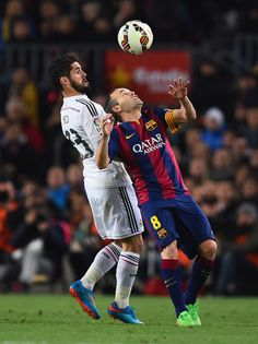 Andres Iniesta of Barcelona is challenged by Isco of Real Madrid CF during the La Liga match between FC Barcelona and Real Madrid CF at Camp Nou on March 22, 2015 in Barcelona, Catalonia.