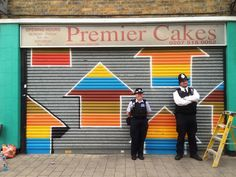 Nothing to see here! Police officers pose with one of the 19 shop shutters painted in 48 hours by US street artist Above over the weekend.