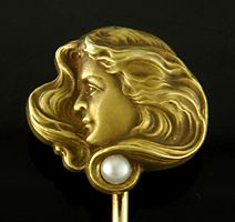 A beautifully sculpted stickpin of a serenely watchful woman with wild, flowing hair.  A small pearl is set in the lower tresses.  A wonderful example of Art Nouveau design.   Crafted in 14kt gold,  circa 1900.