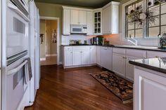 Cozinha tradicional com balcões de granito simples, painel de vidro, Flush, assoalhos de folhosa, painel levantado, U-shaped