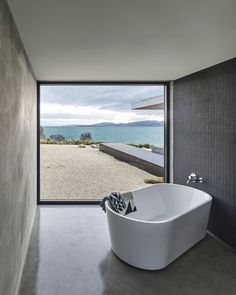 The corner bathroom is defined by a freestanding Kado Lure 1760 tub and a powerful view of the bay.
