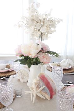 "Thanks so much for stopping by the cottage today!  As our renovations wrap up, I am finally able to take some photos and today I am sharing this ""Coastal-Inspired Valentines Table"" in our dining room! I had so much fun working on this table setting- I used the pretty pink color from the insides of …"