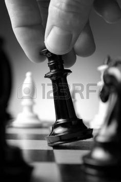 Conceptual image depicting making a strategic move with a hand moving a chess piece on a chessboard during a game of skill photo