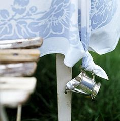 tie a creamer or tea cup to the end of your table cloth to keep the wind from blowing it up