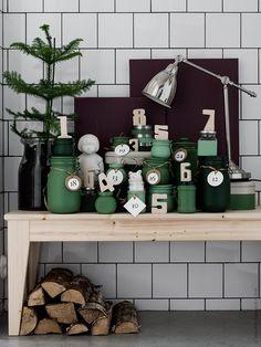 Julkalendern har dukats upp på NORNÄS bänk med BAROMETER arbetslampa. På bänken står en BEGÄRLIG vas där en ARAUCARIA krukväxt rumsgran har planterats. De fina siffrorna i trä som markerar julkalenderns olika luckor är från pusslet PYSSLA plywood.