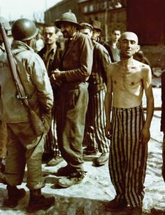In this well-known photograph, American soldiers talk to newly liberated prisoners of the concentration camp at Buchenwald. Some are still wearing their striped prison uniforms, which were supplies to them by the Germans.