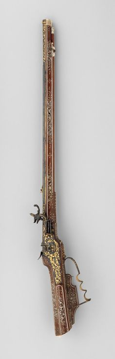 Wheellock rifle. Steel-chiseler: Caspar Spät (German, Munich, ca. 1611–1691). Stock maker: Elias Becker (German, Augsburg, recorded 1633–74). Date: ca. 1640–50. Culture: German, Munich and Augsburg. Medium: Steel, chiseled, blued, and gilt; fruitwood, inlaid with engraved staghorn and bone. | © 2000–2014 The Metropolitan Museum of Art.