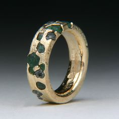 This ring is made by cuttlefish casting and floating stones into the molten metal at the time of casting. The floating stones are suspended in the metal as it hardens. The metal is a custom alloy of 21 karat yellow gold and the stones are rough emeralds and diamonds. www.jewelscurnow.com
