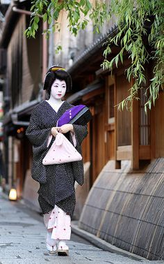 "KYOTO. Gion Machi. The part of town where you'll likely see a geisha. It's more common to see the apprentice ""maiko"" than a geisha. Most people mistake a maiko for a geisha. Maikos wear a dangling obi and dangling hair ornament while geishas do not."