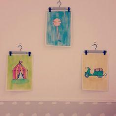 Acuarelas colgadas con mini perchas para la pared de un cuarto infanitl