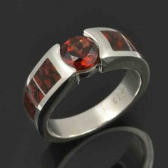 Interesting combination of red fossilized dinosaur bone and a red Mozambique garnet in this unique engagement ring.  The 1.10 carat garnet is set flush with the silver and looks great with the red cells in the dinosaur bone. #DinosaurBoneRing